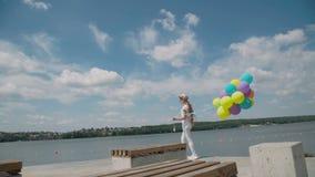 La ragazza graziosa mostra le emozioni felici con i palloni a disposizione al coustline archivi video