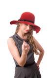 La ragazza graziosa nella grande onda rossa del cappello a voi ha isolato Fotografia Stock