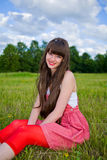 La ragazza graziosa in sarafan rosso si siede su erba verde Fotografia Stock
