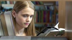La ragazza graziosa sceglie un libro nella biblioteca video d archivio