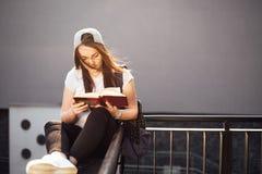 La ragazza graziosa si siede sui punti ed ha letto il libro con le cuffie Immagine Stock