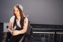 La ragazza graziosa si siede sui punti ed ha letto il libro con le cuffie Fotografia Stock Libera da Diritti