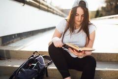 La ragazza graziosa si siede sui punti ed ha letto il libro con le cuffie Immagini Stock Libere da Diritti