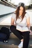 La ragazza graziosa si siede sui punti ed ha letto il libro con le cuffie Immagini Stock