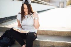 La ragazza graziosa si siede sui punti ed ha letto il libro con le cuffie Immagine Stock Libera da Diritti