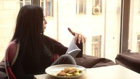 La ragazza graziosa si siede in una sedia e nella lettura del libro stock footage