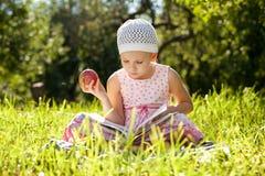 La ragazza graziosa sta leggendo un libro per bambini Fotografia Stock