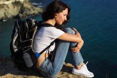La ragazza graziosa sta sedendosi sulla roccia con lo zaino Fotografie Stock