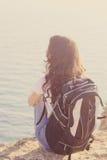 La ragazza graziosa sta sedendosi sulla roccia con lo zaino Fotografie Stock Libere da Diritti