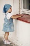 La ragazza guarda alla finestra fotografia stock libera da diritti