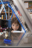 La ragazza guarda la stampante 3D Fotografie Stock Libere da Diritti