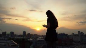 La ragazza guarda nello smartphone contro lo sfondo di un declino giallo Ragazza che per mezzo dello smartphone che si siede sopr video d archivio