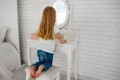 La ragazza guarda nello specchio Dietro la tavola del ` delle signore Tabella di Bathroom immagine stock libera da diritti