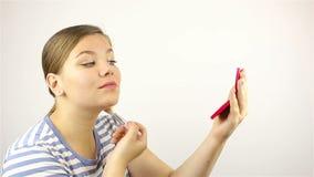 La ragazza guarda nello specchio e spolverizza il suo fronte stock footage