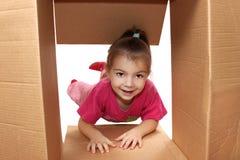 La ragazza guarda in una scatola di cartone Fotografia Stock Libera da Diritti
