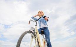 La ragazza guida il fondo del cielo della bici Bici di affitto della donna per esplorare lo spazio della copia della città Gente  immagini stock libere da diritti