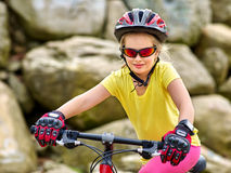 La ragazza guida la bicicletta nel parco delle montagne Fotografie Stock