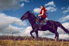 La ragazza guida su un cavallo in vestito rosso che si sviluppa nel campo sul cielo Fotografia Stock