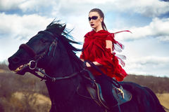 La ragazza guida su un cavallo in vestito rosso che si sviluppa nel campo sul cielo Immagine Stock