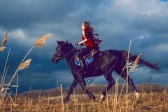 La ragazza guida su un cavallo in vestito rosso che si sviluppa nel campo sul cielo Fotografia Stock Libera da Diritti
