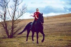 La ragazza guida su un cavallo in vestito rosso che si sviluppa nel campo sul cielo Fotografie Stock
