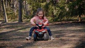 La ragazza guida su un quadrato del giocattolo nella foresta stock footage