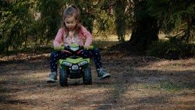La ragazza guida su un quadrato del giocattolo nella foresta archivi video