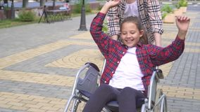 La ragazza guida teenager felice in sedia a rotelle nel parco dell'estate Mo lento video d archivio
