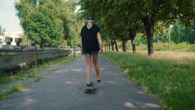 La ragazza guida un pattino sulla via in un parco dell'estate archivi video
