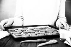 La ragazza ha eliminato i biscotti dello zenzero soltanto dal forno su una lastra di vetro nera Immagini Stock Libere da Diritti