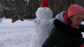La ragazza ha finito di fare un pupazzo di neve nella foresta dell'inverno stock footage
