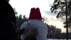 La ragazza ha finito di fare un pupazzo di neve nella foresta dell'inverno archivi video