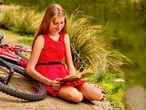 La ragazza ha letto il libro vicino alla bicicletta sulla spiaggia del fiume Fotografia Stock Libera da Diritti