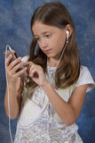 La ragazza ha messo a fuoco sull'applicazione astuta del telefono Immagine Stock