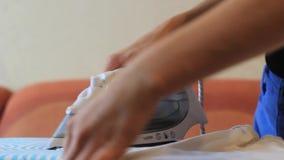 La ragazza ha rivestito di ferro i vestiti con ferro sulla tavola da stiro archivi video
