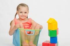 La ragazza ha scalato in una scatola per i giocattoli Fotografia Stock