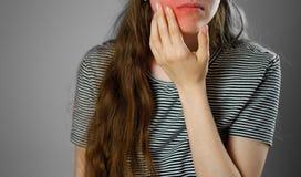 La ragazza ha toccato una consegna il dente facente male Mal di denti Closeu fotografia stock