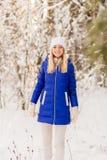 La ragazza ha un resto nel legno dell'inverno fotografia stock