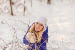 La ragazza ha un resto nel legno dell'inverno immagini stock