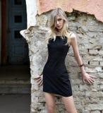 La ragazza il blonde in un vestito nero Immagine Stock