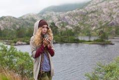 La ragazza il turista in montagne ha riscaldato una tazza di tè caldo fotografia stock