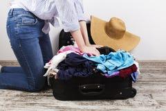 La ragazza imballa con indifferenza la valigia nera fotografie stock