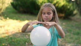 La ragazza imita lo stregone che ondeggia le sue mani sopra la sfera bianca stock footage