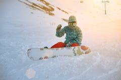 La ragazza impara lo snowboard in montagne all'inverno Immagine Stock