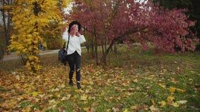 La ragazza incantante cammina nel parco colourful di autunno, mette sopra il cappello ed i sorrisi video d archivio