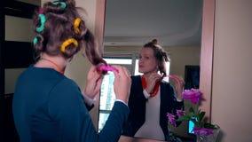 La ragazza incinta dei giovani decolla i bigodini che guardano in specchio e si ammira stock footage