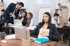 La ragazza incinta dei giovani sta lavorando nell'ufficio con i colleghi Donna di affari incinta in ufficio immagine stock