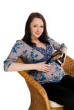 La ragazza incinta ha messo i trasduttori auricolari su uno stomaco Fotografia Stock
