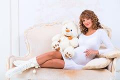 La ragazza incinta Redheaded in un vestito tricottato con l'orsacchiotto riguarda lo strato Immagini Stock Libere da Diritti