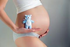 La ragazza incinta sta contro la parete Fotografia Stock